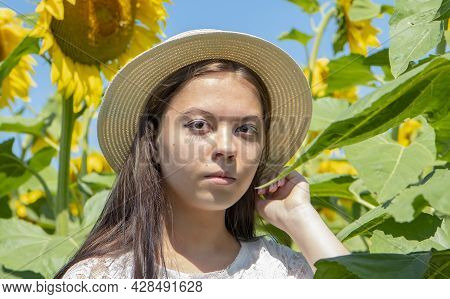 Portrait Of A Serious Young Girl Of 17-20 Years Old In A Straw Hat Against A Background Of Blooming