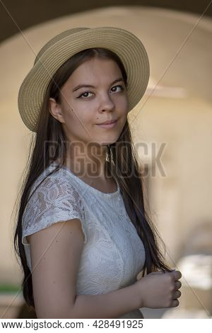 A Young Girl Of 17-20 Years Old In A White Dress And A Straw Hat Stands Under A Stone Arch And Smile