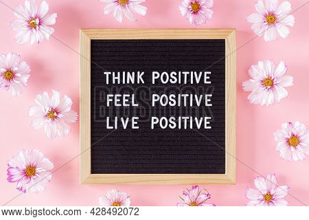 Think Positive, Feel Positive, Live Positive. Motivational Quote On Letter Board And Flowers On Pink