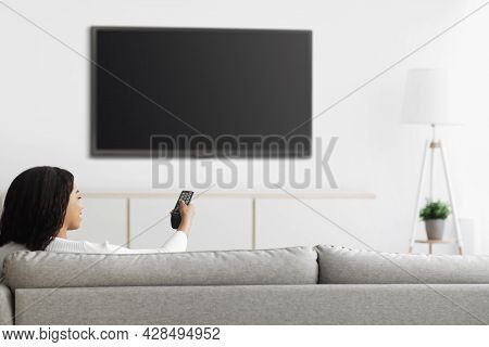 African American Woman Watching Tv Pointing Remote Control At Flatscreen Plasma Television Set With