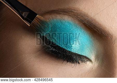 Applying Cyan Eye Shadow Onto Woman's Face, Closeup. Beautiful Evening Makeup