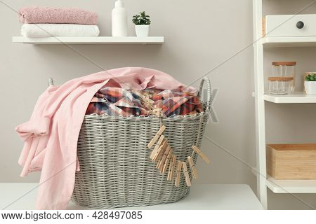 Wicker Basket With Dirty Laundry And Clothespins On Table Indoors
