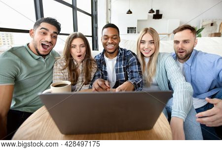 Diverse Young Friends Using Laptop At Table Indoors, Watching Movie, Communicating Online, Having Vi