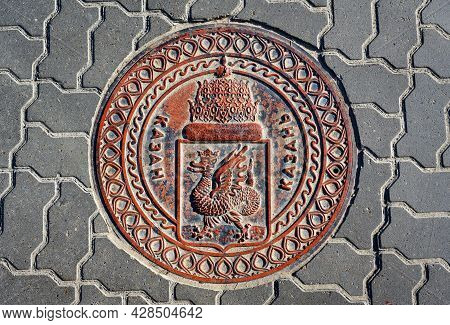 Manhole Cover In Kazan, Tatarstan, Russia. Sewer Lid With Coat Of Arms Of Kazan On Road. Top View Of