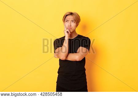 Indecisive Moody Asian Guy Sulking, Looking Away Thoughtful, Standing Over Yellow Background, Making