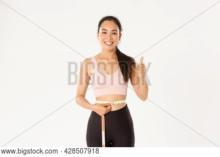 Fitness, Healthy Lifestyle And Wellbeing Concept. Portrait Of Satisfied Smiling, Cute Asian Girl In