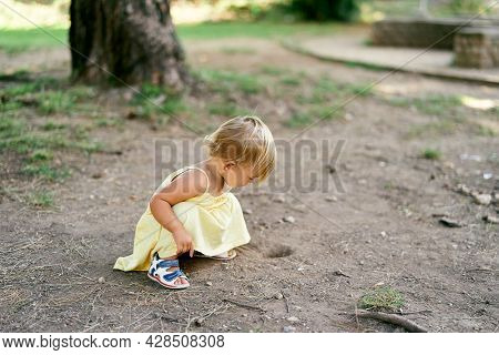 Little Girl Squatted Near A Hole In The Ground Near A Tree