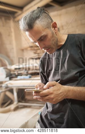Carpenter Artisan Resting In Workshop And Scrolling On Smartphone. Handsome Handicraftsman Texting M