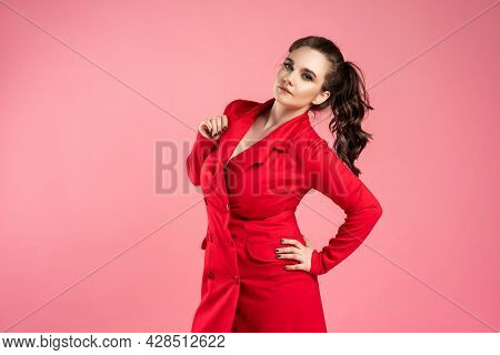 Beautiful Young Woman In Red Coat On Pink Background