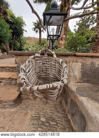 Empty Rustic Basket Hanging On Stone Bench With Black Rustic Garden Lantern. Wicker Basket Hung On A