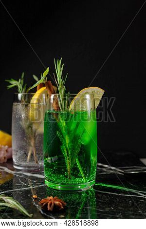 Refreshing Carbonated Drink Of Bright Green Color, Tarragon And A Glass Of Tonic In The Background.