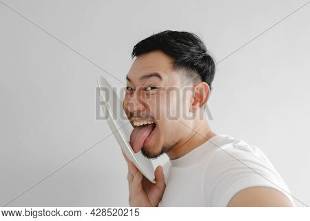 Funny Face Asian Man Is Licking White Dish In Concept Of Very Delicious Meal.