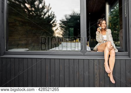 Young Woman Resting At Modern House Or Hotel In Pine Forest, Sitting On The Window Dangling Her Legs