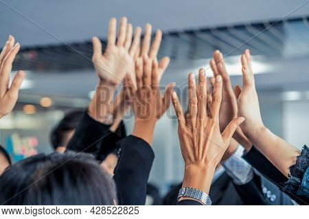 Many Happy Business People Raise Hands Together With Joy And Success. Company Employee Celebrate Aft