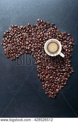 Roasted Coffe Beans Shaping Map Of The Africa On Blackboard With Cup Of Coffee. Major World Coffee P