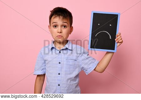 A Frustrated Boy In A Blue Shirt Holds A Blackboard Near His Face With A Painted Emoticon Expressing