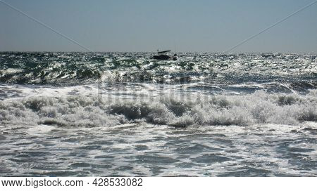 Beautiful Blue Sea Waves With White Foam Close Up. Bustling, Violent Ocean And Horizon In Background