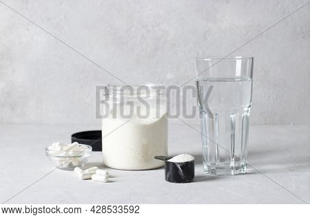 Collagen Powder In A Jar And Measuring Spoon, Collagen Capsules And A Glass Of Water On Gray Backgro
