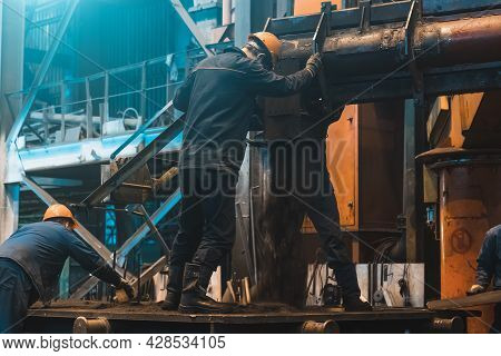 Workers In Process Of Work With Large Mold Iron Cast On Steel Mill. Foundry Workshop Interior. Typic