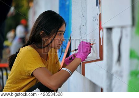 Young Girl Draws On The Street. Drawing On The Wall. Creative Child, Girl Portrait Close-up. Pencils