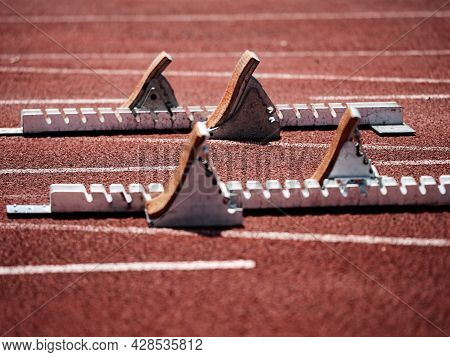 Starting Blocks On Light Red Running Tracks Lanes At Track And Field Stadium. Sport Accessory.