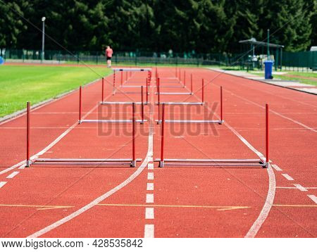 Fallen Hurdle On The Sprint Lane With Starting Blocks Against Blurry Background. Stadium With Two Hu