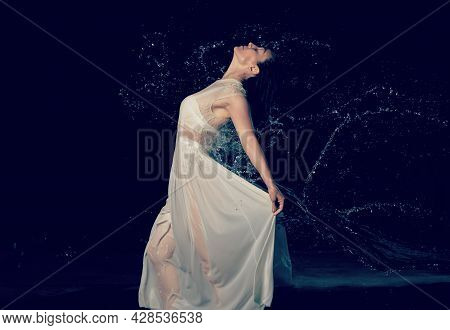 Beautiful Woman Of Caucasian Appearance With Black Hair Dances In Drops Of Water On A Black Backgrou