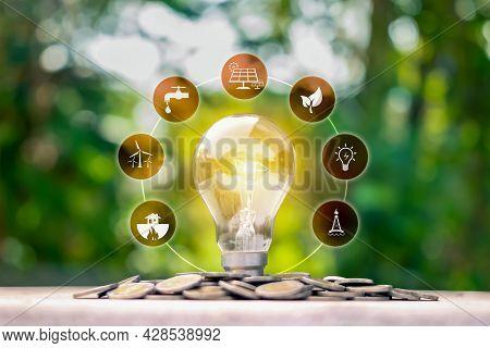 Glowing Energy-saving Lamp And Energy Icon On The Coin, Money-saving Concept. Energy Saving And Envi