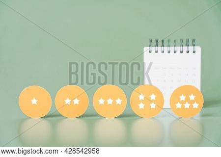 Rating Stars On Yellow Circle Paper With Blurred White Calendar, Ranking, Survey, Feedback, Satisfac