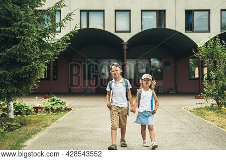 Two Caucasian Children, Boy And Girl, Walking To School With Bags Behind Their Backs And Books. Stud