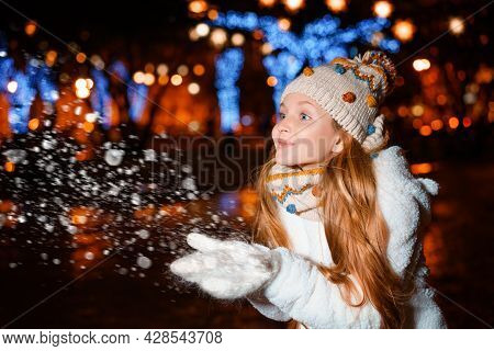 A Blonde Teenager With Long Hair In A Hat And Winter Clothes On A Festive Winter Evening On The Stre