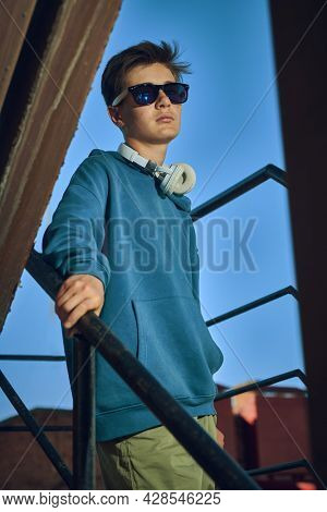 Youth style. A modern teenage boy in a hoodie, headphones and sunglasses standson the stairs against the background of the city. Youth fashion.