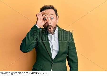 Middle age man wearing business suit doing ok gesture shocked with surprised face, eye looking through fingers. unbelieving expression.
