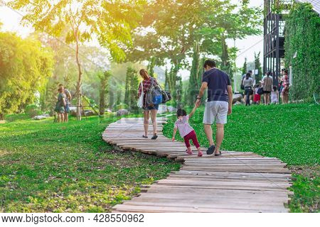 Back View Of Asian Father Hand Holding Lovely Daughter Walking On Pathway Through Green Garden.dad A