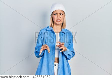 Beautiful blonde woman wearing wool hat disgusted expression, displeased and fearful doing disgust face because aversion reaction.