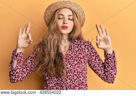 Beautiful blonde caucasian woman wearing summer hat relax and smiling with eyes closed doing meditation gesture with fingers. yoga concept.