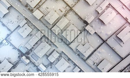Aerial. Suburban Cottages In Winter. Top View From Drone. It's Snowing.