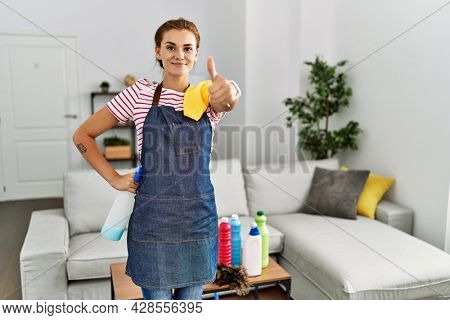 Young brunette woman wearing apron holding cleaning products at home doing happy thumbs up gesture with hand. approving expression looking at the camera showing success.