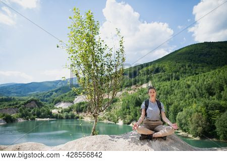Mid Adult Woman Tourist On Hiking Trip On Summer Holiday, Doing Yoga And Meditating.