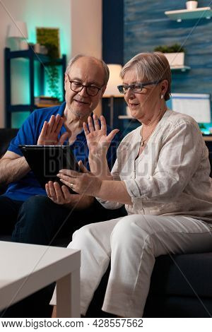 Married Couple Using Video Call Technology Waving At Webcam For Online Internet Conference On Modern