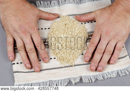 Dried White Uncooked Grains Of Rice Lie On A White Ethnic Fringed Towel. A Portion Of Rice Grits And