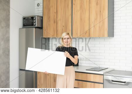 White Canvas In Female Hands With Gray Wall Background. Woman Hanging Blank Picture Mockup On Wall W