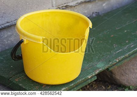 Empty Dirty Broken Yellow Plastic Bucket On Green Bench