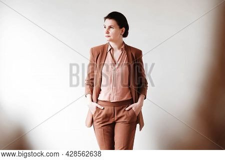 Woman Dressed In A Brown Business Suit On A White Background. Copy, Empty Space