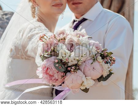 Picture Of Man And Woman With Bouquet. Married Couple Holding Hands, Ceremony Wedding Day. Newly Wed