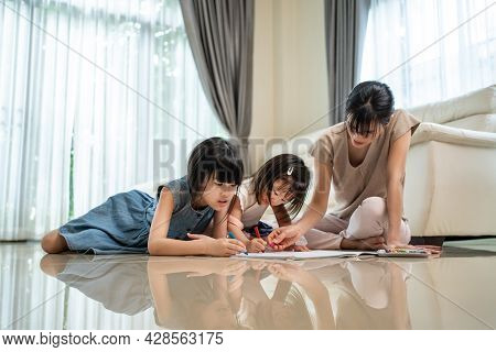 Asian Little Siblings Girl Draw And Color Picture With Mother On Floor. Beautiful Loving Parent, Mom