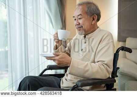 Asian Senior Disabled Man Drinking Coffee Enjoy Stay Nursing Home Care. Mature Elderly Older Guy Sit