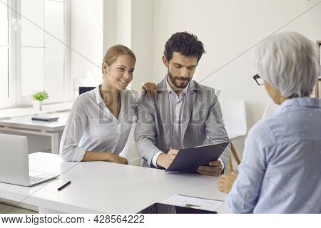 Young Couple Signing Contract During Meeting With Mortgage Agent, Realtor Or Loan Broker