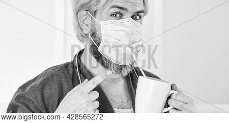 Serious About Hygiene. Guy In Mask Drink Tea Coffee Using Straw. Cover Mouth And Nose With Mask And