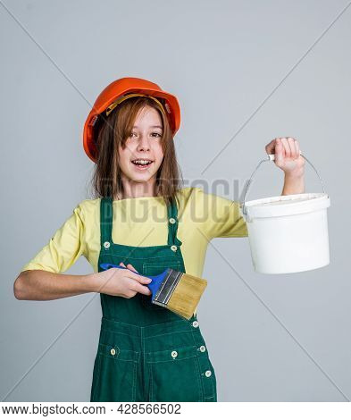 Teen Girl Laborer In Protective Helmet And Uniform Use Painting Brush And Bucket, Labor Day